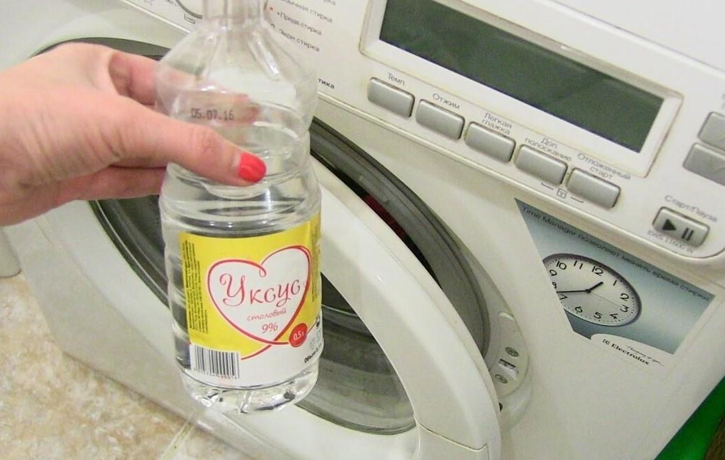 Бутылка уксуса возле стиральной машинки