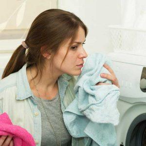 Девушка держит в руке полотенце после стирки